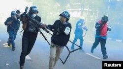 Các phóng viên bỏ chạy khi cảnh sát bắn gas khống chế biểu tình tại Bangkok, 16 tháng Tám. Hình minh họa.