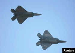 FILE - Two US F-22 fighter jets are seen in flight.