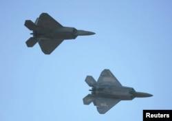 ເຮືອບິນຮົບ ອາຍພົ່ນ ສະຫະລັດ F-22 ສອງລຳ ແມ່ນເຫັນບິນຢູ່ ເທິງໜ່ານຟ້າ.