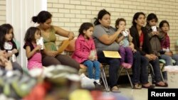 Migrants sit at the Sacred Heart Catholic Church temporary migrant shelter in McAllen, Texas, June 27, 2014.