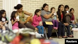 FILE - Migrants sit at the Sacred Heart Catholic Church temporary migrant shelter in McAllen, Texas, June 27, 2014.