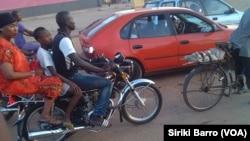 Un moto-taxi à côte d'un taxi à Bouaké, en Côte d'Ivoire, le 5 juin 2017. (VOA/Siriki Barro)