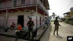FILE - Panamanian border police patrol a street in Puerto Obaldia near the Colombian border in Panama, Sept. 16, 2015.