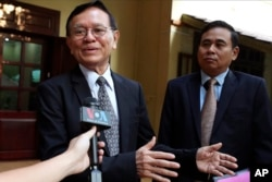 Cambodia's opposition leader Kem Sokha, left, talks to the media at his home before leaving for the court hearing in Phnom Penh, Thursday, Jan. 16, 2020. (AP photo)