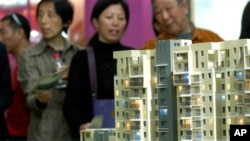 南京的市民在房地產交易會上觀看公寓樓的模型。