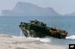FILE - A U.S. Navy's amphibious assault vehicle with Philippine and U.S. troops on board storms the beach at a combined assault exercise at a beach facing one of the contested islands in the South China Sea known as the Scarborough Shoal in the West Philippine Sea Tuesday, April 21, 2015.