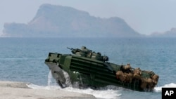 FILE – A U.S. Navy amphibious assault vehicle storms the beach in a joint exercise with American and Filipino troops at an island in the contested Scarborough Shoal, claimed by the Philippines and China, April 21, 2015.