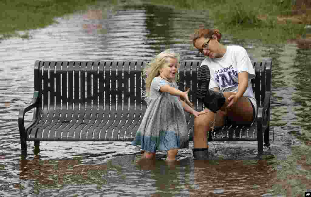 Katie Bender gets some assistance from Johanna Bender (L) as they dump water from a boot while sitting on a flooded street after Hurricane Arthur passed through in Manteo, N.C.