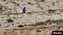 Daredevil Nik Wallenda gives a thumbs-up sign as he nears the end, after walking on a two-inch (5-cm) diameter steel cable rigged 1,400 feet (426.7 metres) across more than a quarter-mile deep remote section of the Grand Canyon near Little Colorado River
