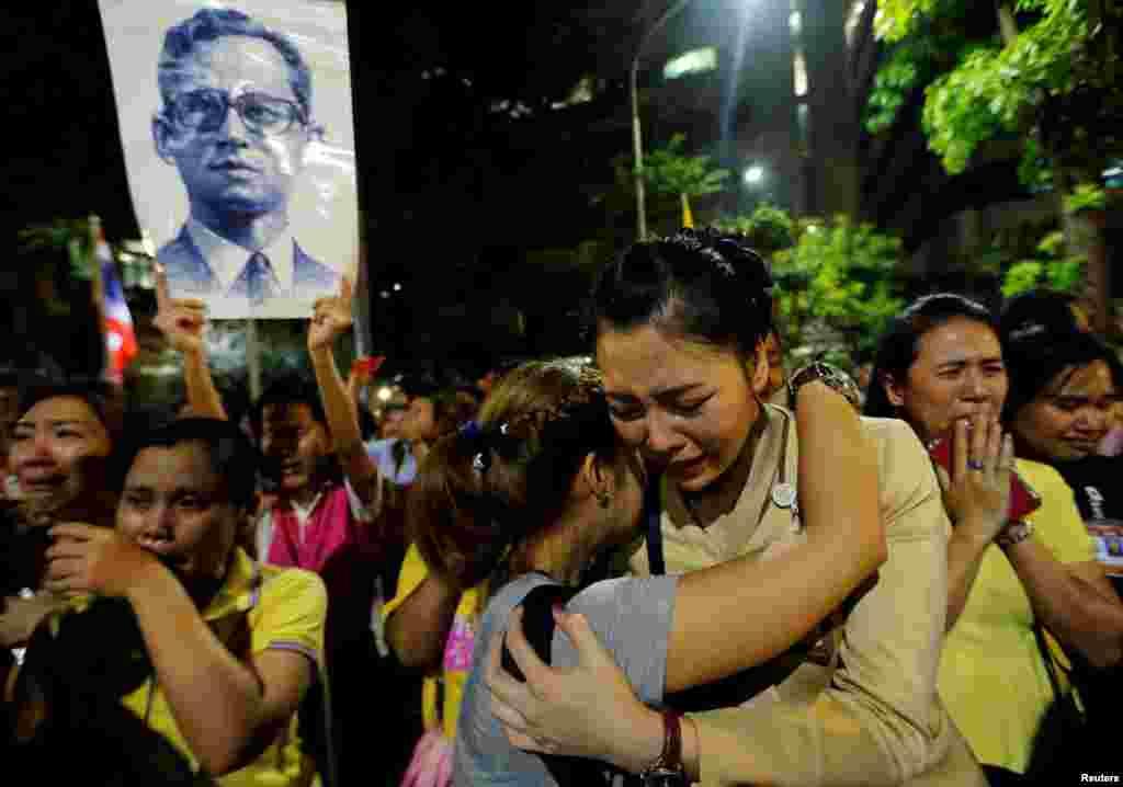 ស្រ្តីពីរនាក់យំឱបគ្នានៅខាងក្រៅមន្ទីរពេទ្យ Siriraj ទីដែលព្រះមហាក្សត្រថៃព្រះបាទ Bhumibol Adulyadej សម្រាកព្យាបាលព្រះកាយ ក្នុងក្រុងបាងកក ប្រទេសថៃ។