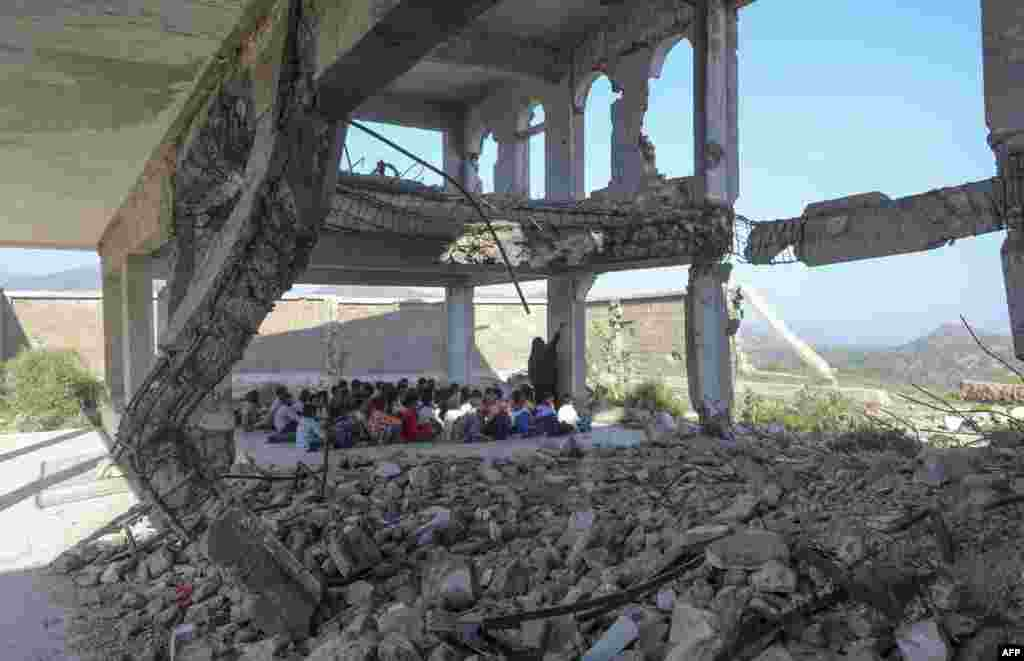 Yemeni pupils attend class on the first day of the new academic year, in a makeshift classroom in their school compound which was heavily damaged two years ago in an airstrike, in the country's third-city of Taez.