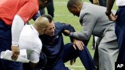 Gary Kukiak, entrenador de los Tejanos de Houston es ayudado a levantarse.