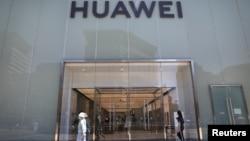 人們走過北京街頭的華為專賣店。 (2021年6月3日)