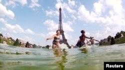 Anak-anak bermain air di air mancur Alun-Alun Trocadero di depan Menara Eiffel dalam sore musim panas yang terik di Paris (19/7). (Reuters/Gonzalo Fuentes)