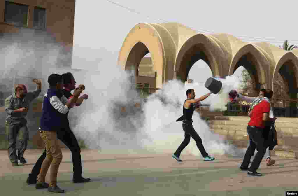 A man uses a bucket to put out a tear gas canister as Coptic Christians run inside the Saint Mark Coptic cathedral during clashes with Muslims, April 7, 2013.