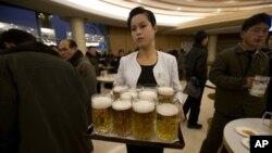 Seorang pramusaji Korea Utara menyajikan bir di restoran Mansugyo Soft Drink di Pyongyang. (Foto: Dok)