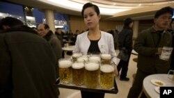 지난 20일 북한 평양 만수교청량음료점에서 한 여종업원이 맥주를 나르고 있다. 김정은 국방위원회 제1위원장의 지시로 리모델링을 했으며, 7가지 맛의 맥주와 칵테일, 커피 등을 판매하고 있다.