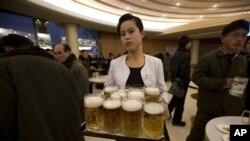 지난 2012년 북한 평양 만수교청량음료점에서 한 여종업원이 맥주를 나르고 있다. (자료사진)