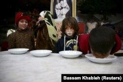 Orphelins buvant du lait offert par une association caritative à Harasta, dans la banlieue de Damas en Syrie, le 30 janvier, 2016. (Reuters / Bassam Khabieh)