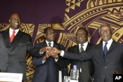 FILE - Officials join hands at the signing of the power-sharing deal in Harare, Zimbabwe, Sept, 15, 2008. From left: Arthur Mutmbara, deputy prime minster; Robert Mugabe, president; Morgan Tsvangirai, prime minster; and Thabo Mbeki, South Africa's president.