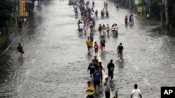 Cư dân đi bộ trên một đường phố ngập nước ở ngoại ô Pasig City, phía đông Manila, Philippines, ngày 9/8/2012