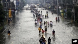 People walk on a flooded street in suburban Pasig City, east of Manila, Philippines, August 9, 2012.