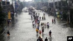 八月九号在马尼拉东郊人们在街道上涉水而行