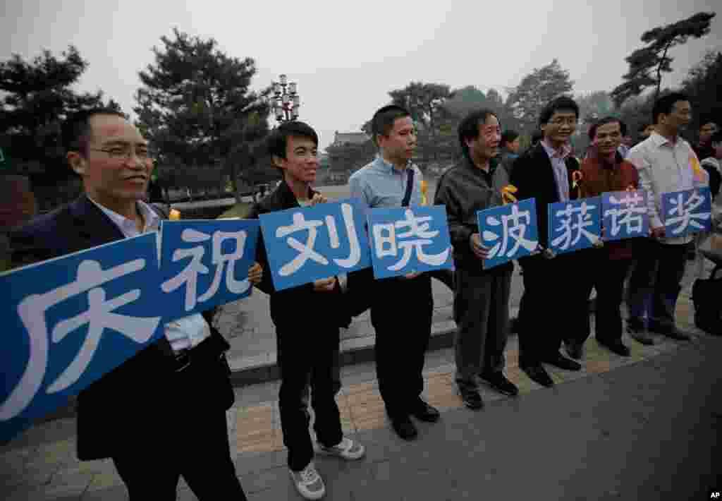 """2010年10月8日,正在監牢服刑的""""零八憲章""""起草人之一,中國民主運動人士劉曉波獲得諾貝爾和平獎的消息傳來,他的支持者在北京一個公園外面展示標語""""慶祝劉曉波獲諾獎""""。"""