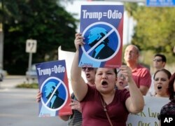 "Berta Sandes, 38, of Miami, an undocumented immigrant from Nicaragua, holds a sign that translates to ""Trump Equals Hate"" during a protest against then-Republican presidential candidate Donald Trump outside the Trump National Doral golf resort, March 14, 2016, in Doral, Fla."