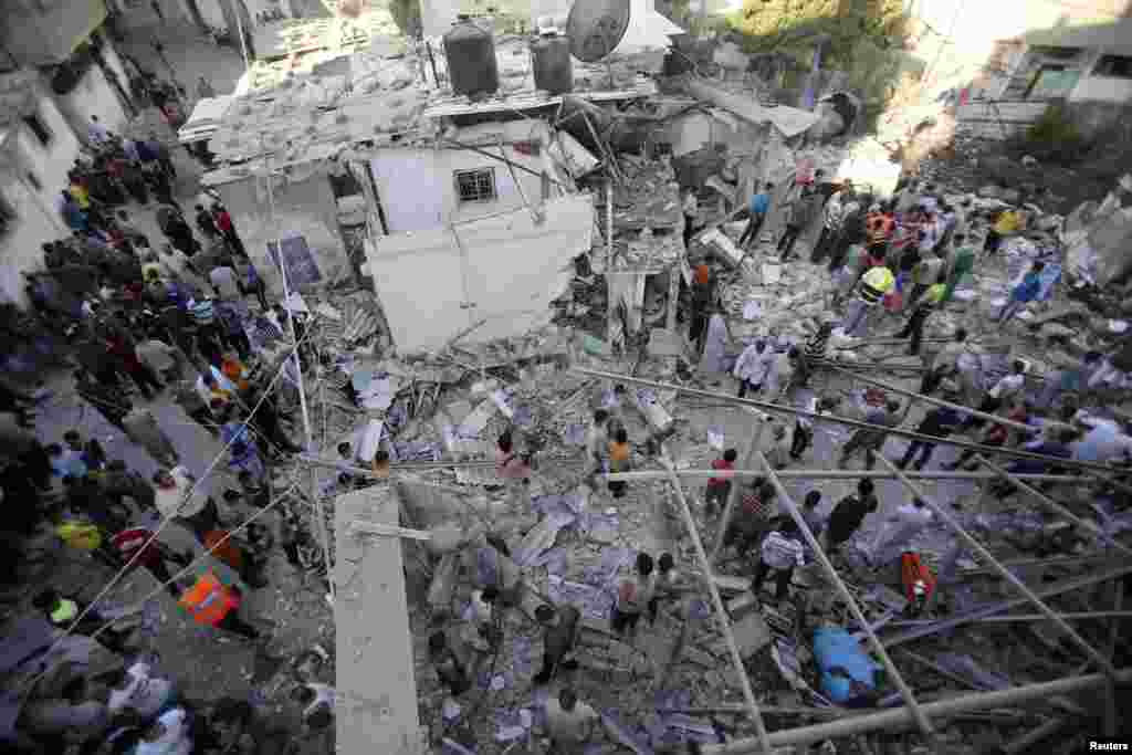 Rescue workers search for victims as Palestinians gather around the wreckage of a house, which witnesses said was destroyed in an Israeli airstrike that killed at least nine members from the al-Ghol family, in Rafah, southern Gaza Strip, August 3, 2014.