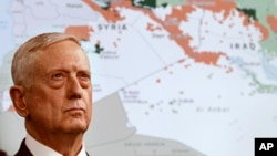 FILE - Secretary of Defense Jim Mattis stands in front of a map of Syria and Iraq, while speaking to the media about the Islamic State group at the Pentagon, May 19, 2017.