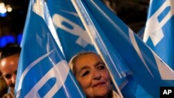 A supporter of Conservative Popular Party candidate Mariano Rajoy celebrates the results of the national election polls in Madrid, Spain, Sunday, Nov. 20, 2011.