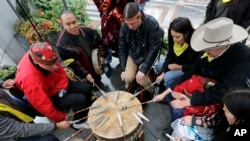 Native Americans and First Nations people join in on a drum circle during an Indigenous Peoples Day blessing and rally before a march Monday, Oct. 8, 2018, in Seattle. (AP Photo/Elaine Thompson)