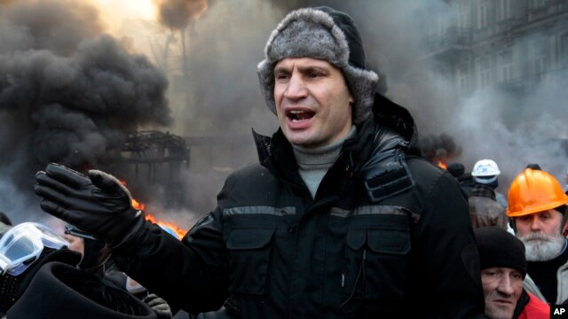 Opposition leader and former WBC heavyweight boxing champion Vitali Klitschko addresses protesters near the burning barricades between police and protesters in central Kyiv, Jan. 23, 2014.