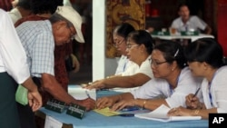 在缅甸仰光的一个投票站,一个选民签名领取选票(2017年4月1日)