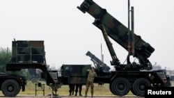 FILE - Dutch soldiers are seen standing next to a Patriot missile battery at a military base in Adana, southern Turkey, Jan. 26, 2013.