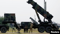 Dutch soldiers are seen standing next to a Patriot missile battery at a military base in Adana, southern Turkey, January 26, 2013.