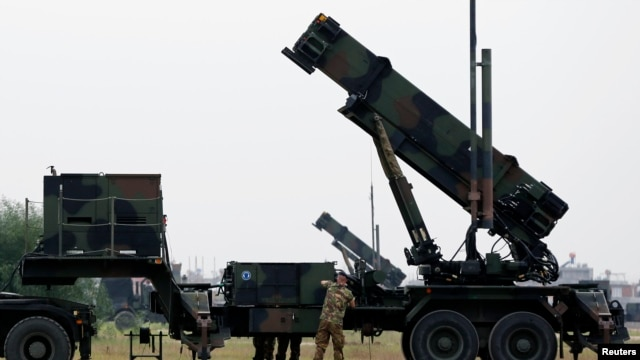 FILE - Dutch soldiers are seen standing next to a Patriot missile battery at a military base in Adana, southern Turkey, January 26, 2013.