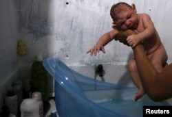 FILE - Daniele Santos, 29, holds her son Juan Pedro who was born with microcephaly, after bathing him at their house in Recife, Brazil, Feb. 9, 2016.