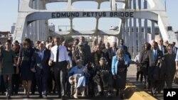 """Chantant """"We Shall Overcome"""", le président Barack Obama, quatrième de la gauche, marche tenant la main avec Amelia Boynton, qui a été tabasséu lors de """"Bloody Sunday"""", avec la première famille et d'autres personnes"""
