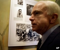 FILE - U.S. Sen. John McCain, R-Ariz, is seen during a tour of Hoa Lo Prison site, Hanoi, April 8, 2009. The photo behind McCain is that the Hanoi army and people pull out McCain out of Truc Back Lake on Oct. 26, 1967 after his plane was shot down.
