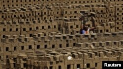FILE - A laborer carries bricks at a kiln in Karjat, India, March 10, 2016. Thousands of brick kiln workers in India's western Maharashtra state are learning from activists that they have the right to a minimum wage, basic amenities and fair treatment.
