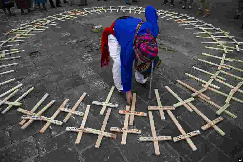 A Mayan spiritual guide arranges crosses with the names of people who died in the nation's civil war, which ended in 1996, in a circle for a ceremony marking National Day of Dignity for the Victims of Armed Internal Conflict, at the National Palace in Gua