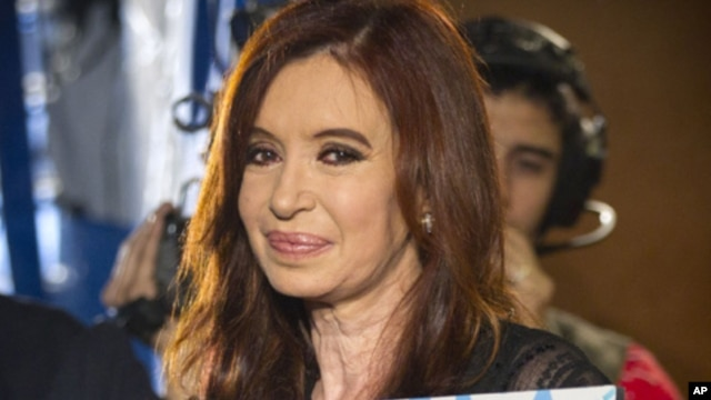 Argentina's President Cristina Fernandez holds a photo of her late husband and former Argentine President Nestor Kirchner at the Plaza de Mayo square after general elections in Buenos Aires, Argentina, Sunday, Oct. 23, 2011.
