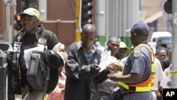 FILE: Zimbabweans pass a police cordon to submit their application forms outside the Immigration offices in Johannesburg, in a last minute bid to have their status in South Africa legalized (File Photo)