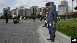 Một người đàn ông cúi đầu về phía Cung điện Hoàng gia khi nghe phát biểu của Nhật hoàng tại Tokyo, 8/8/2016.