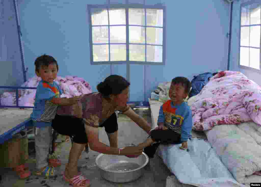 A woman washes the feet for a crying child under a tent at a quake zone at Longtoushan, Dudian county, in Zhaotong, Yunnan province, Aug. 5, 2014.