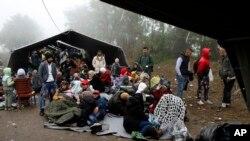 一群移民在塞尔维亚贝尔格莱德以西大约100公里处的塞尔维亚与克罗地亚的边界等候过境。(2015年10月18日)