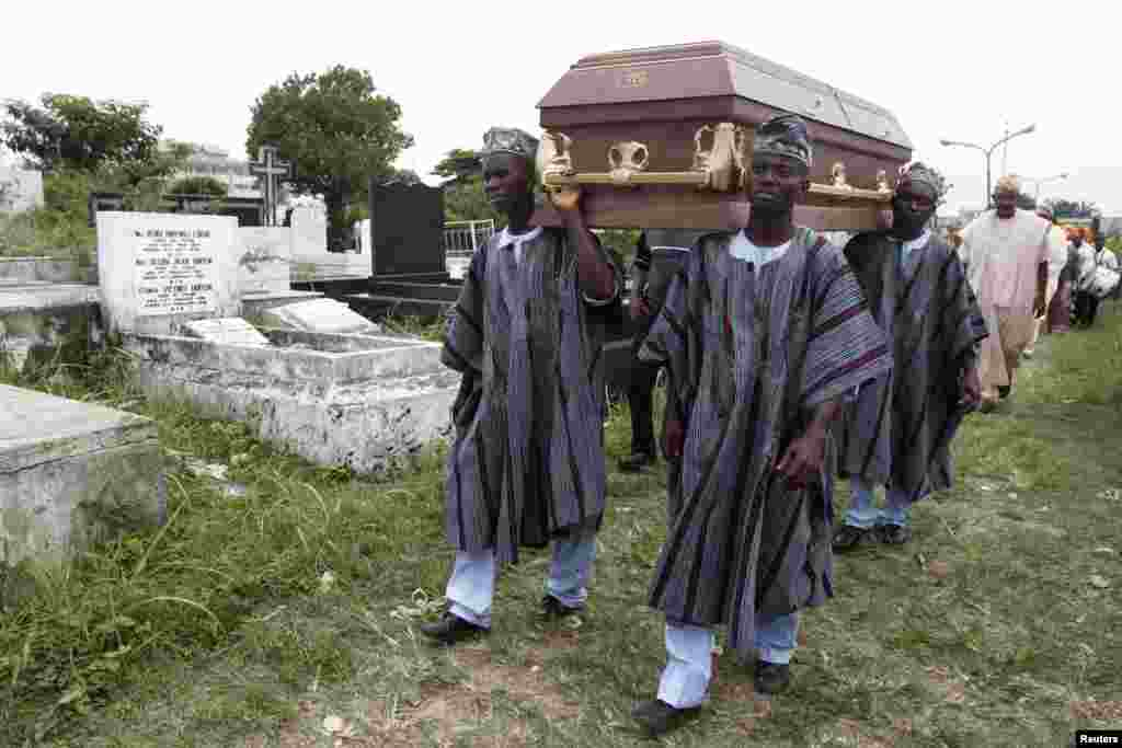 Pallbearers carry a coffin through a cemetery during a funeral ceremony in Lagos, Nigeria, May 31, 2013.
