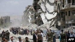 Les forces pro-gouvernementales se tiennent dans la rue détruite de Thalateen, dans la banlieue sud de la capitale, Damas, le 24 mai 2018.